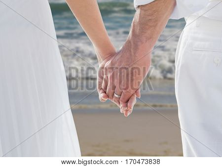 Close-up of newly wed couple holding hands on beach