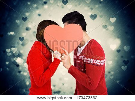 Romantic couple holding heart shape and kissing each other against digitally generated background