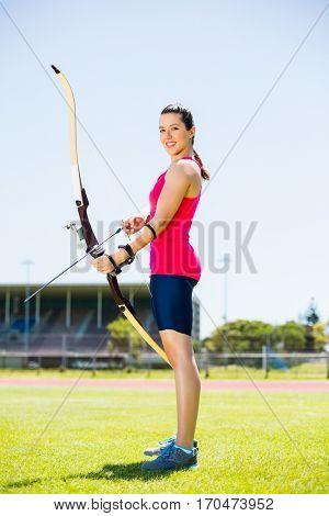 Portrait of female athlete practicing archery in stadium