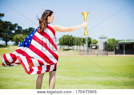 Female athlete wrapped in american flag holding fire torch in stadium