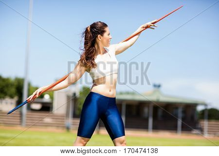 Female athlete carrying javelin on her shoulder and standing in stadium