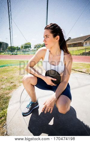 Confident female athlete holding a discus in stadium