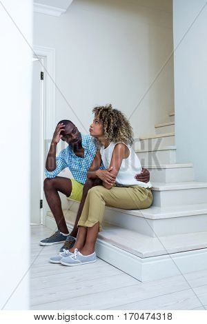 Young couple at home sitting on steps and talking
