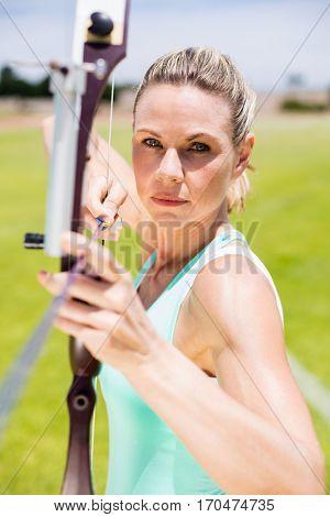 Confident female athlete practicing archery in stadium