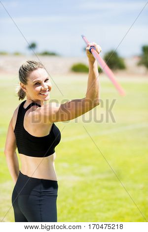 Portrait of female athlete about to throw a javelin in the stadium