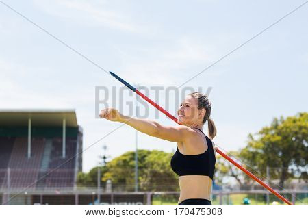 Happy female athlete about to throw a javelin in the stadium