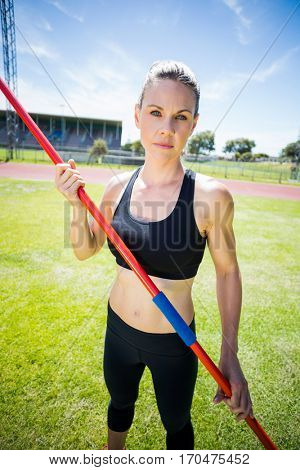 Portrait of female athlete holding a javelin standing in stadium
