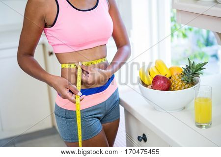 Mid-section of woman measuring her waist at home