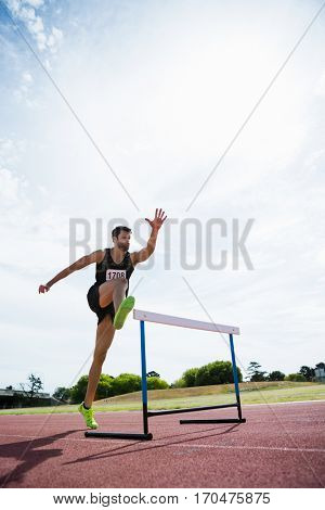 Athlete jumping above the hurdle during the race