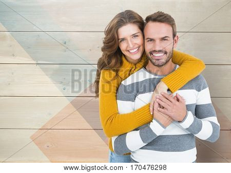 Portrait of romantic couple embracing each other against wooden background