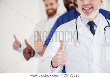 Your health is in good hands. Cheerful bearded physicians standing while demonstrating approval sign with thumb up