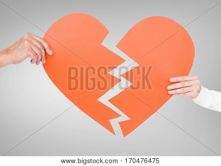 Hand of couple holding broken hearts against grey background