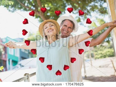Portrait of romantic couple standing with arms outstretched with digitally generated of heart