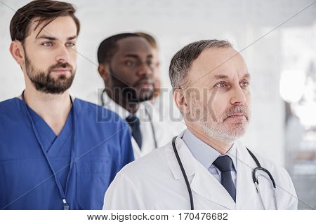 Serious bearded therapeutics standing in white hospital room during conference