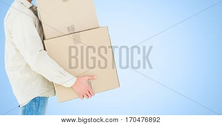 Mid section of delivery man holding cardboard box against blue background