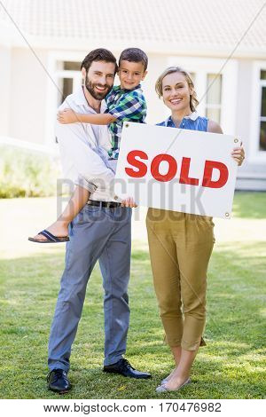 Portrait of happy family standing outside home with sold sign