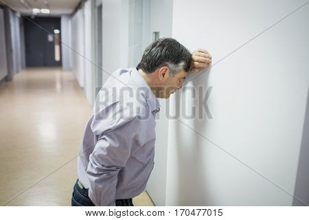 Worried professor leaning on wall in corridor