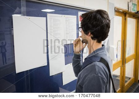 Student reading notice board in college