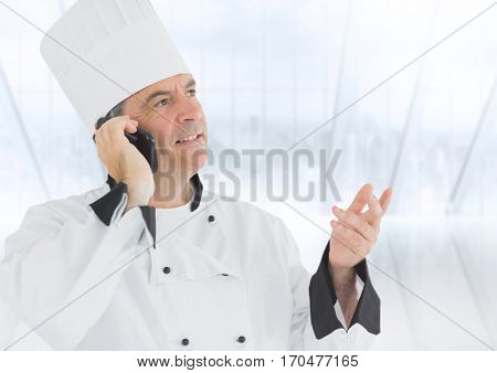 Chef talking on mobile phone against white background