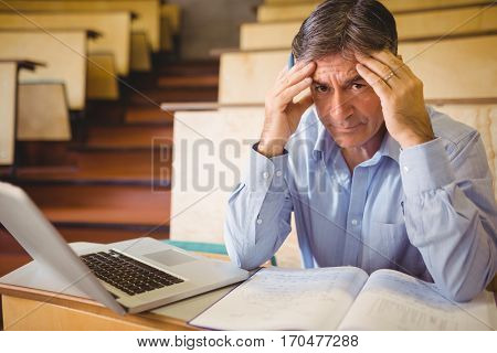 Depressed professor sitting with notes and laptop in classroom