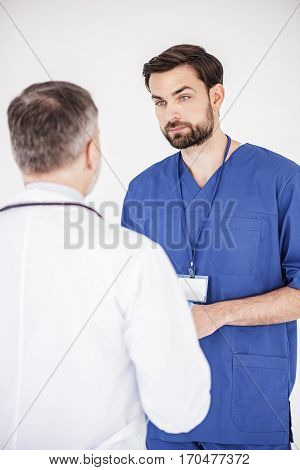 Serious physician discussing with his partner while they standing opposite each other in hospital office