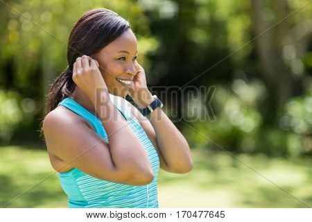 Happy woman listening music in the park