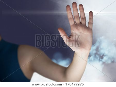 Digital composite image of womans hand touching virtual screen against sky background