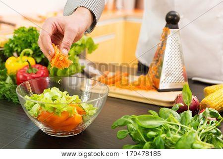 vegan food - preparing vegetable salad with grated carrots