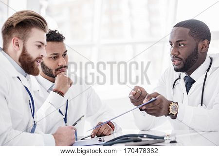 Serene medical advisers discussing x-ray photo at conference in white hospital room. Willing african doctor showing image to his colleagues while sitting at table