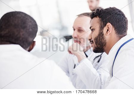 Calm young asian therapeutic listening his partners at meeting in apartment of clinic