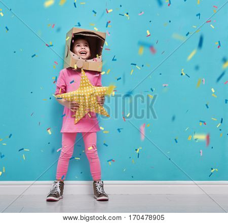 Child girl in an astronaut costume is playing and dreaming of becoming a spacemen. Portrait of funny kid on a background of bright blue wall with confetti.