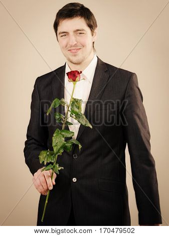Smart clothing for guys. Elegant young man with red rose. Handsome boy wearing black classic suit and white shirt.