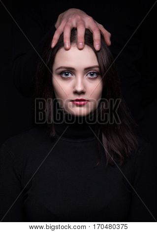 Attractive woman with man's hands on black background