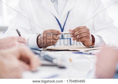 close up hands of doctor holding pen in his hand while leaning on table at conference in office of clinic