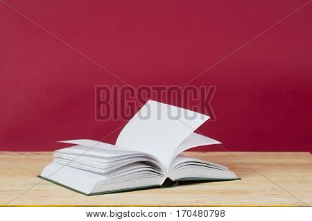 Open book on wooden table. Back to school. Red background. Copy space.
