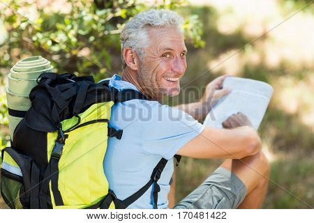 Hiker smiling and holding a map on the wood