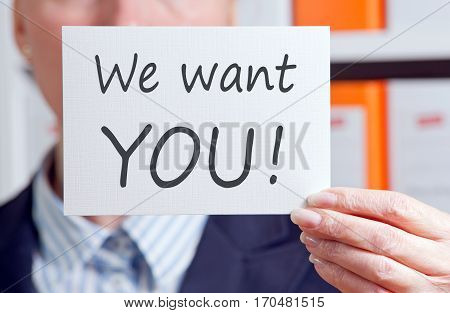 We want you - Businesswoman holding sign with text in the office