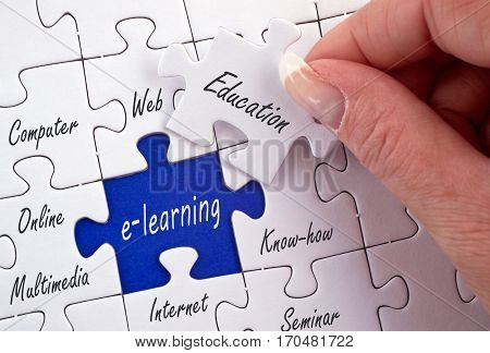 E-learning - education puzzle with female hand and text