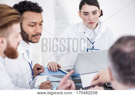 Calm medical advisers discussing image of patient during conference in white office of clinic. Willing female therapeutic listening her colleagues while sitting at table