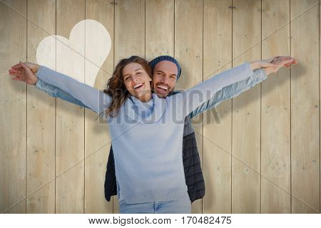 Happy couple standing with arms outstretched against wooden planks