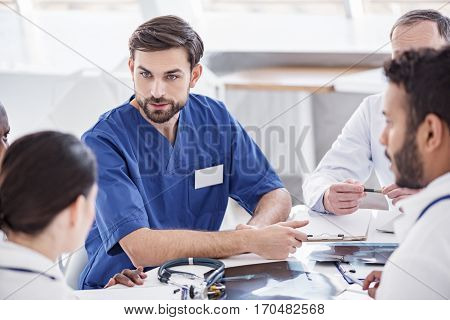Willing bearded medical adviser discussing with colleagues while leaning on surface of table at conference in office of clinic
