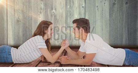 Happy couple arm wrestling against wooden shelf on gray wall