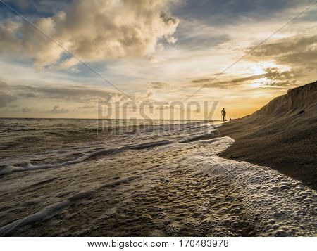 Silhouette of young woman doing Nordic walking on the beach against the sunrise sky