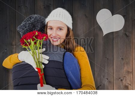 Couple hugging each other with red roses against wooden planks
