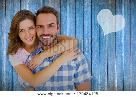 Happy young couple embracing against wooden planks
