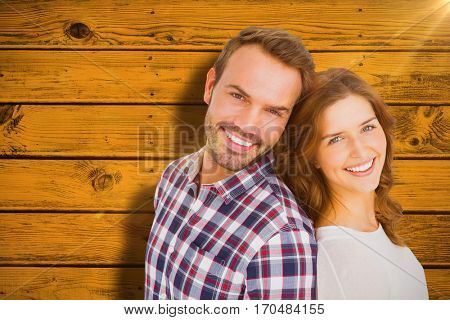 Close up of happy young couple standing back to back against yellow paint splashed surface