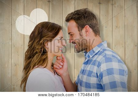 Happy young couple looking at each other and smiling against wooden planks