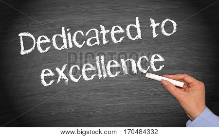 Dedicated to excellence - female hand writing text