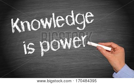 Knowledge is power - female hand writing text on chalkboard