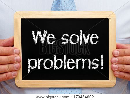 We solve problems - businessman holding chalkboard with text